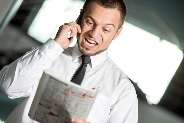 O homem está procurando emprego no jornal e chamando.