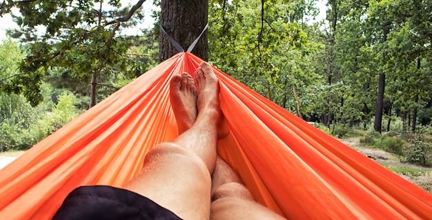 O homem está relaxando e relaxando na rede no acampamento