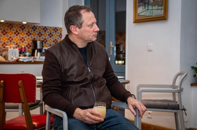 O homem está relaxando em casa e bebendo um copo de álcool