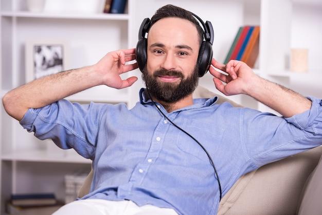 O homem está relaxando em casa, ouvindo música usando fone de ouvido.