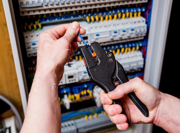 O homem está reparando a tensão do painel de distribuição com interruptores automáticos.