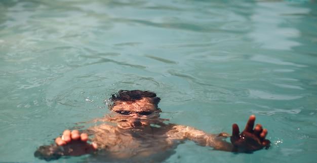 O homem está se afogando na água. conceito de natação de segurança.