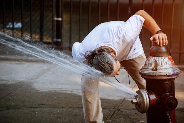 O homem está se refrescando em alta temperatura pública de verão quadrado com água de hidrante