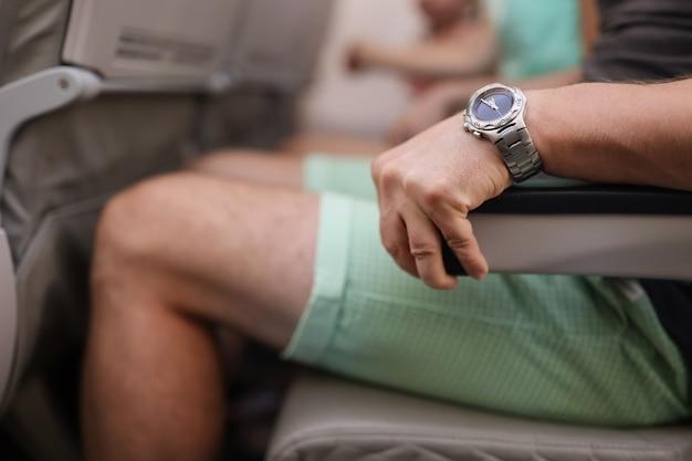 O homem está segurando com força o corrimão do assento do avião