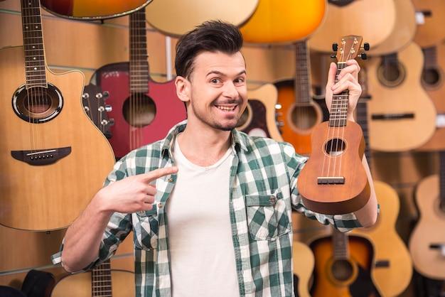 O homem está segurando o ukelele na loja da música.