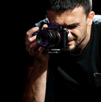 O homem está segurando uma câmera e pronto para atirar. o fotógrafo olha pelo visor da câmera e tira fotos.