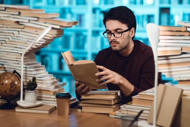 O homem está sentado à mesa, rodeado por livros na biblioteca.