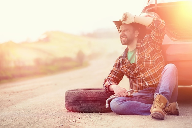 O homem está sentado na estrada perto do carro na natureza