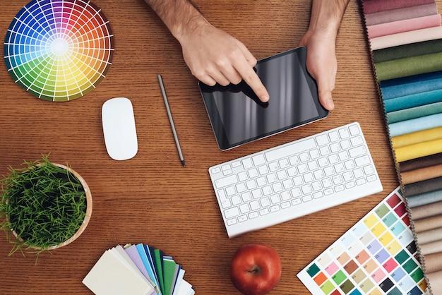 O homem está sentado no laptop. ele trabalha em um escritório criativo.