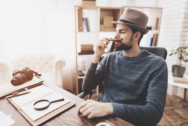 O homem está sentando-se na tabela que cheira sigar.