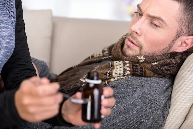 O homem está sofrendo de um resfriado. mulher lhe dá remédio.