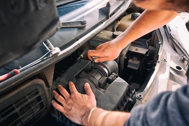 O homem está tentando consertar o carro velho quebrado em casa