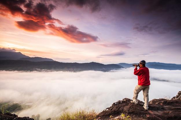 O homem está tirando fotos do mar de neblina na alta montanha.