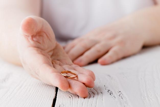 O homem está tirando o anel de casamento