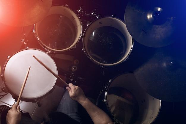 O homem está tocando bateria em plano de baixa luminosidade.