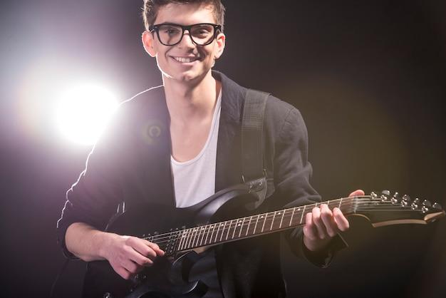 O homem está tocando violão no quarto escuro com luzes atrás dele.