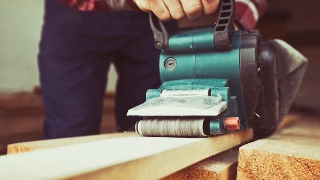 O homem está trabalhando com madeira