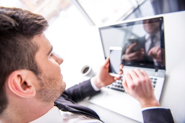 O homem está trabalhando com o portátil e está prendendo um telefone móvel.