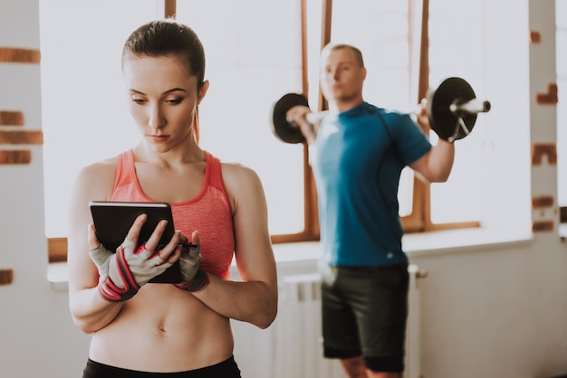 O homem está treinando com barbell. mulher está usando tablet.