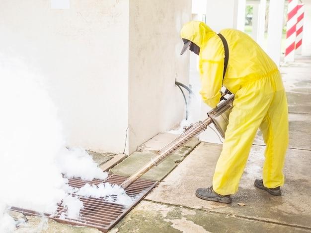 O homem está usando a máquina de névoa térmica para proteger a propagação do mosquito