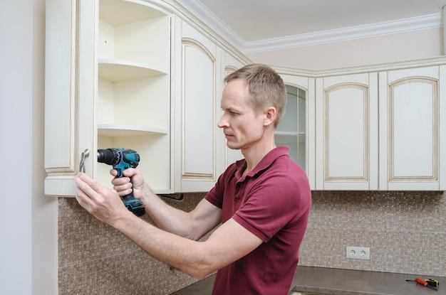 O homem está usando uma chave de fenda para ajustar a porta curva do armário.