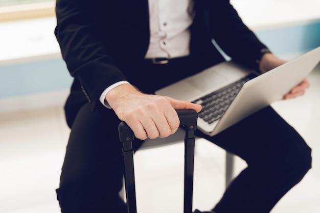 O homem está vestido com um terno preto. ele segura um laptop.