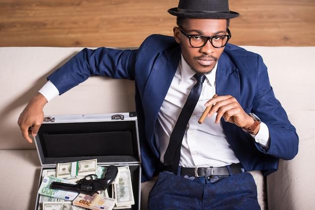 O homem está vestindo terno e chapéu com arma e dinheiro.