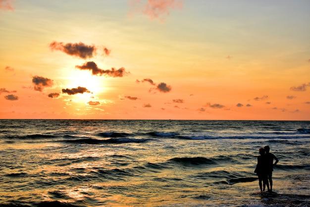 O homem estava de pé junto ao mar com a mulher nos braços e observava o sol nascer de manhã