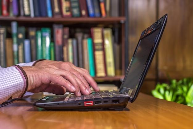 O homem estava digitando algo em seu laptop