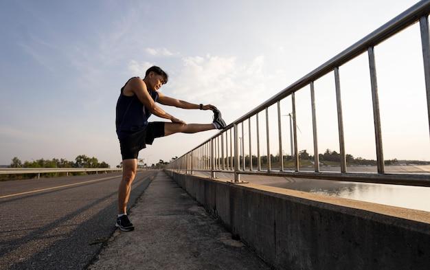 O homem estica o corpo antes de correr. fitness, corrida, corrida, exercício, estilo de vida e conceito saudável.