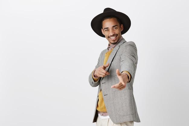 O homem estiloso encantava as meninas com seu carisma. foto interna de um homem elegante e bonito em roupas formais e chapéu, apontando e sorrindo amplamente, feliz e de bom humor sobre uma parede cinza
