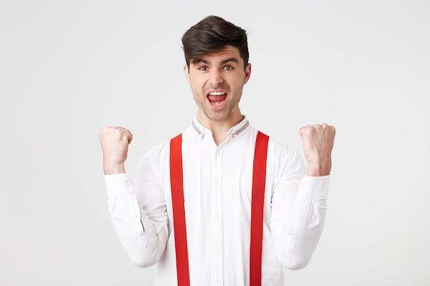 O homem exultante fecha os punhos de felicidade, abre amplamente a boca enquanto grita alto, comemora seu sucesso