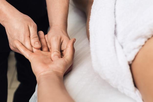 O homem faz massagem nas palmas das mãos e nos dedos no spa. conceito de estilo de vida saudável.