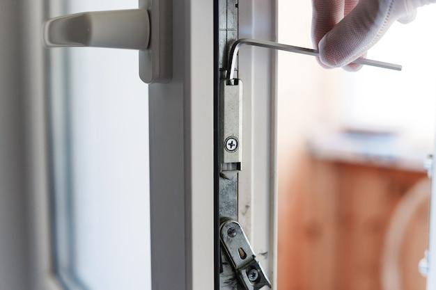O homem faz o ajuste do mecanismo da porta de pvc com uma chave allen.