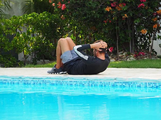 O homem faz um exercício de imprensa perto da piscina