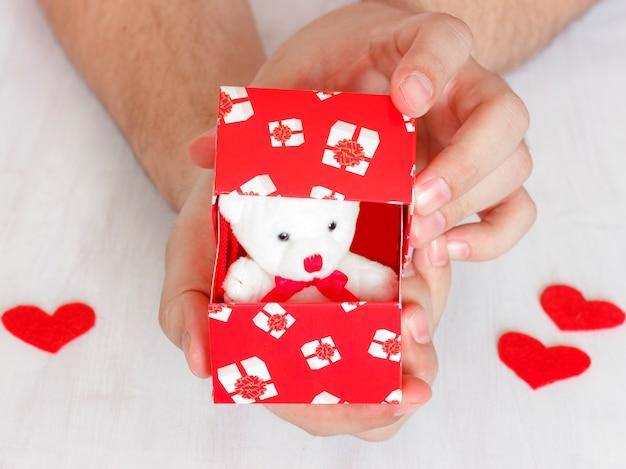 O homem faz uma proposta. urso de pelúcia em uma caixa vermelha com corações como um presente