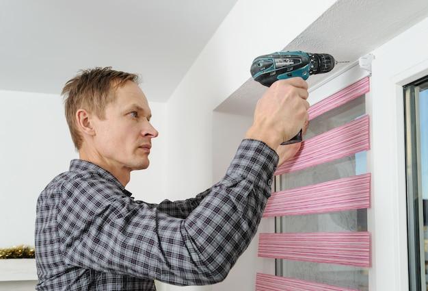 O homem fazendo furos para consertar cortinas de tecido