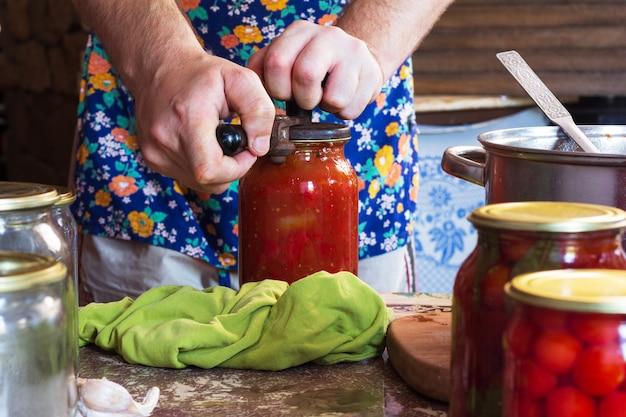 O homem fecha com frascos de tomate em conserva e um molho de farinha em uma cozinha rústica em um dia de verão