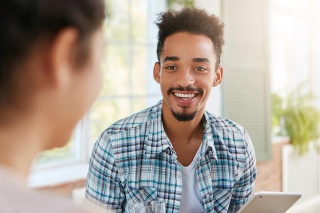 O homem feliz e positivo de pele escura tem barba e bigode, sorri amplamente, demonstra dentes brancos,