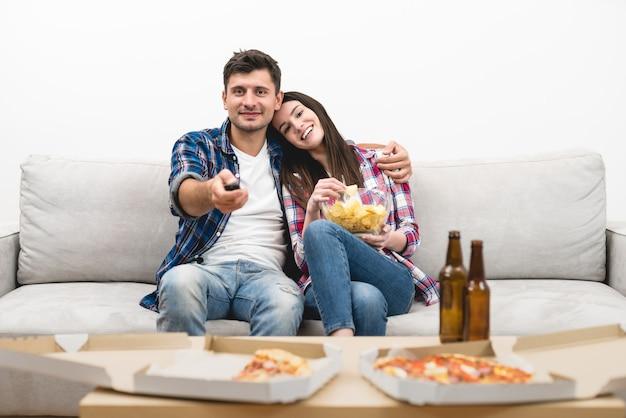 O homem feliz e uma mulher assistem televisão no fundo da parede branca