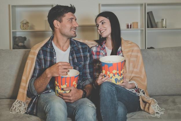 O homem feliz e uma mulher comendo pipoca e assistindo filme no sofá