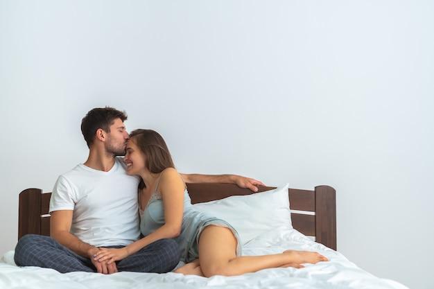 O homem feliz e uma mulher se beijando na cama no fundo branco
