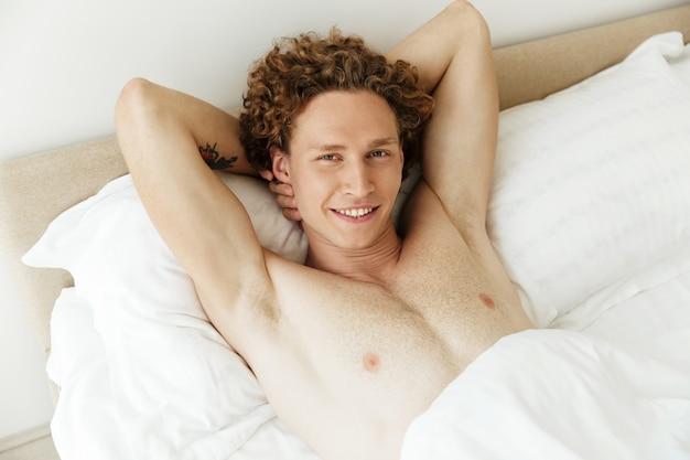 O homem feliz encontra-se na cama em casa