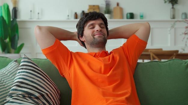 O homem feliz está descansando em um sofá confortável, com os olhos fechados