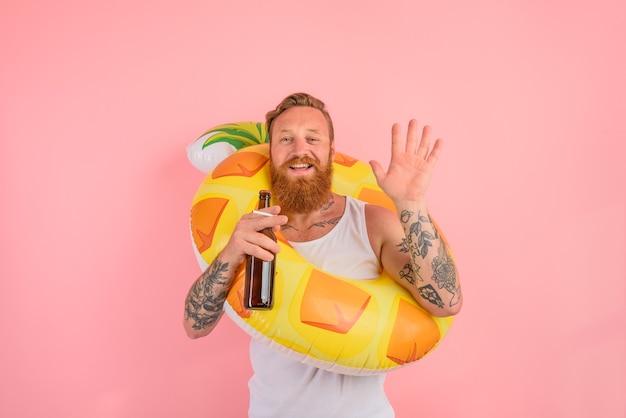 O homem feliz está pronto para nadar com um salva-vidas de donut com cerveja e cigarro na mão