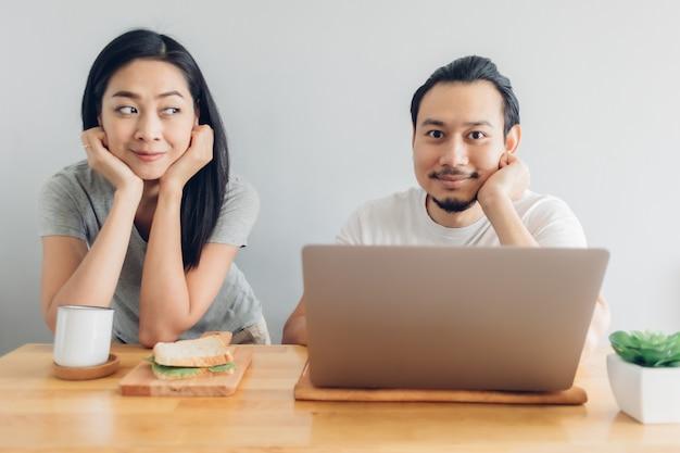 O homem feliz está trabalhando on-line com o apoio da esposa