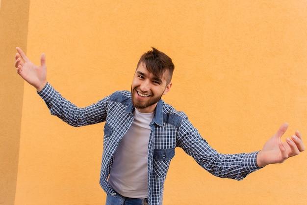O homem feliz faz um gesto com a mão contra o pano de fundo de uma parede laranja