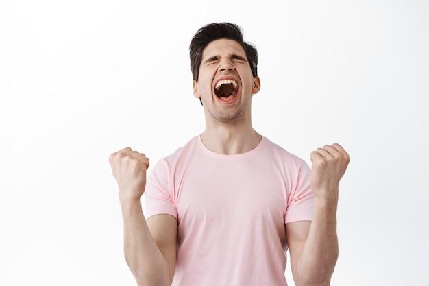 O homem feliz grita em comemoração, ganhando o prêmio, gritando de alegria, cerrando os punhos como campeão, celebrando a vitória e o triunfo, alcançar o sucesso do objetivo, de pé sobre a parede branca
