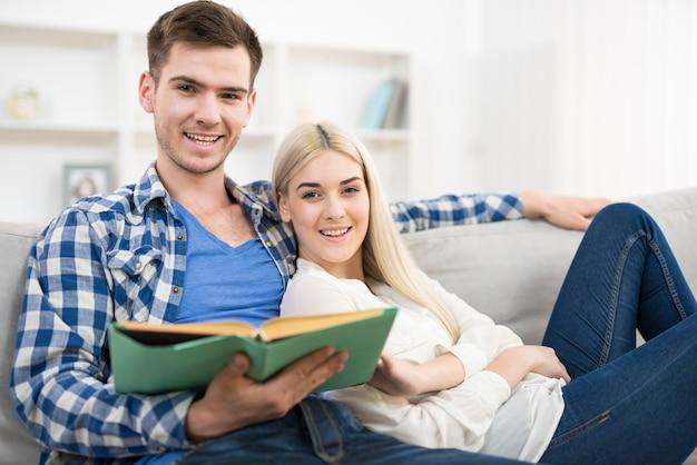 O homem feliz lendo o livro perto da mulher em um sofá