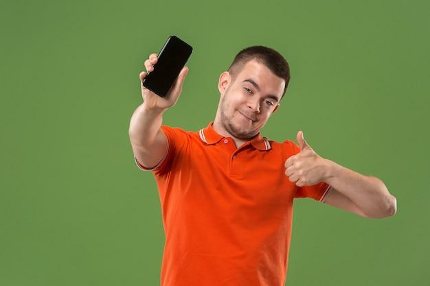 O homem feliz mostrando a tela vazia do telefone móvel contra verde.